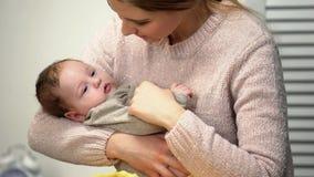 Uśmiechnięta matka podziwia nowonarodzonej córki, trzyma dziecka i patrzeje z miłością, zdjęcia stock