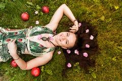 Uśmiechnięta miedzianowłosa alternatywna dziewczyna z ogolonymi spacerami w Pogodnym Jabłczanym sadzie na Pogodnym letnim dniu zdjęcia stock