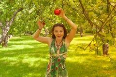 Uśmiechnięta miedzianowłosa alternatywna dziewczyna z ogolonymi spacerami w Pogodnym Jabłczanym sadzie na Pogodnym letnim dniu zdjęcia royalty free