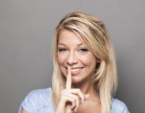 Uśmiechnięta modna kobieta pyta utrzymywać zaciszność dla dyskreci fotografia stock