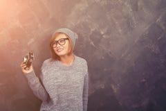Uśmiechnięta modniś kobieta jest ubranym szkła trzyma retro kamery agę Fotografia Stock