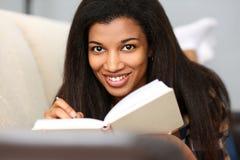 Uśmiechnięta murzynka pisze opowieści w notatniku fotografia royalty free