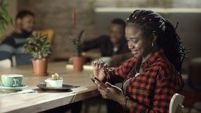 Uśmiechnięta murzynka z telefonem w kawiarni zbiory wideo