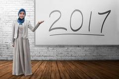 Uśmiechnięta muzułmańska biznesowa kobieta pokazuje 2017 na desce Obrazy Stock