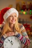 Uśmiechnięta nastolatek dziewczyna w Santa kapeluszu z zegarem Fotografia Royalty Free