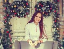 Uśmiechnięta nastoletnia dziewczyna ma zabawę nad boże narodzenie dekoraci backgr Obrazy Royalty Free