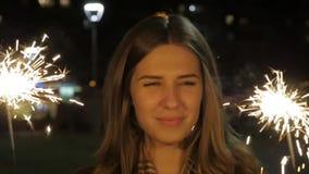 Uśmiechnięta nastoletnia dziewczyna na ulicie przy nocą z sparklers Młoda kobieta świętuje wydarzenie nowy rok przychodzi zbiory wideo