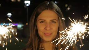 Uśmiechnięta nastoletnia dziewczyna na ulicie przy nocą z sparklers Młoda kobieta świętuje wydarzenie nowy rok przychodzi zbiory