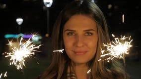 Uśmiechnięta nastoletnia dziewczyna na ulicie przy nocą z sparklers Młoda kobieta świętuje wydarzenie nowy rok przychodzi zdjęcie wideo
