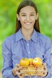 Uśmiechnięta nastoletnia dziewczyna z koszem jabłka Obraz Stock