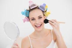 Uśmiechnięta naturalna brown z włosami kobieta w włosianych curlers stosuje proszek na jej twarzy Fotografia Stock