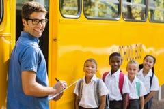 Uśmiechnięta nauczyciela aktualizowania czeka lista dzieciaki podczas gdy wchodzić do w autobusie fotografia stock