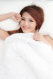 Uśmiechnięta nieśmiała azjatykcia kobieta pod duvet Zdjęcia Stock