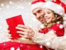 Uśmiechnięta ojca i córki czytelnicza książka Zdjęcia Stock