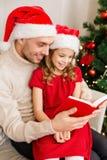 Uśmiechnięta ojca i córki czytelnicza książka Obraz Stock