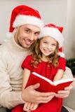 Uśmiechnięta ojca i córki czytelnicza książka Zdjęcie Royalty Free