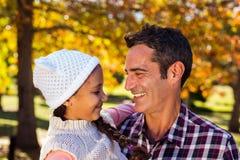 Uśmiechnięta ojca przewożenia córka przy parkiem Fotografia Royalty Free