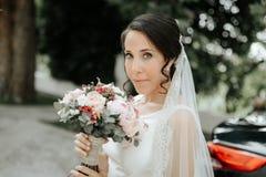 Uśmiechnięta panna młoda trzyma bridal bukiet w ślubnej sukni i przesłona zdjęcie stock
