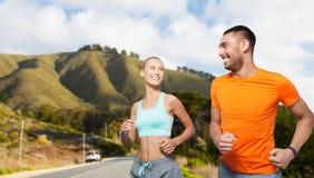 Uśmiechnięta para biega nad dużymi sur wzgórzami Obraz Royalty Free