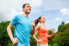 Uśmiechnięta para biega outdoors Fotografia Stock