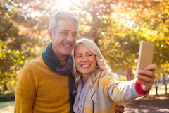 Uśmiechnięta para bierze selfie przy parkiem Zdjęcie Stock