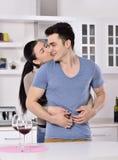 Uśmiechnięta para cieszy się czerwonego winogradu w kitchev zdjęcie stock