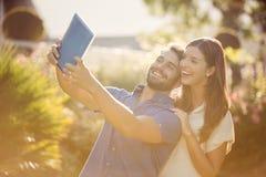 Uśmiechnięta para klika selfie z cyfrową pastylką Obrazy Stock