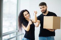 Uśmiechnięta para odpakowywa pudełka w nowym domu fotografia stock