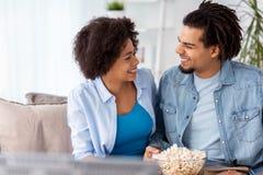 Uśmiechnięta para ogląda tv w domu z popkornem Fotografia Royalty Free
