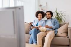 Uśmiechnięta para ogląda tv w domu z popkornem Zdjęcia Royalty Free