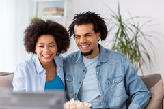 Uśmiechnięta para ogląda tv w domu z popkornem Zdjęcie Stock