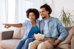 Uśmiechnięta para ogląda tv w domu z popkornem Obrazy Royalty Free
