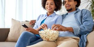 Uśmiechnięta para ogląda tv w domu z popkornem Zdjęcie Royalty Free