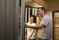 Uśmiechnięta para patrzeje płytkę dla łazienki w sklepie obraz royalty free