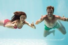 Uśmiechnięta para pokazuje aprobaty podczas gdy pływający obraz stock