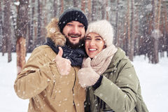 Uśmiechnięta para pokazuje ok gest pod opadem śniegu w myst Obrazy Royalty Free