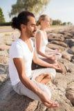 Uśmiechnięta para robi joga ćwiczy outdoors Fotografia Royalty Free