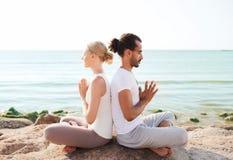 Uśmiechnięta para robi joga ćwiczy outdoors Zdjęcie Stock