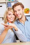 Uśmiechnięta para trzyma małego dom Zdjęcie Stock