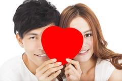 Uśmiechnięta para trzyma miłość znaka Obrazy Royalty Free