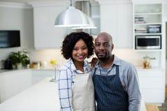 Uśmiechnięta para w fartuch pozyci przy kuchnią obrazy royalty free