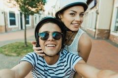 Uśmiechnięta para w hełmach bierze selfie outdoors zdjęcie stock