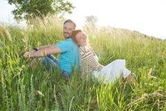 Uśmiechnięta para w lato trawie na zmierzchu szczęśliwy mężczyzna i kobiety obsiadanie w polu popierać z powrotem fotografia royalty free