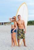 Uśmiechnięta para w okularach przeciwsłonecznych z surfuje na plaży Fotografia Stock