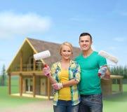 Uśmiechnięta para w rękawiczkach z farba rolownikami Zdjęcia Stock