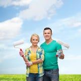 Uśmiechnięta para w rękawiczkach z farba rolownikami Obraz Stock