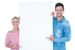 Uśmiechnięta para wskazuje przy pustym miejscem podpisuje wewnątrz ich ręki Obraz Royalty Free