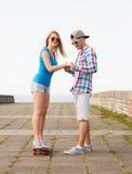 Uśmiechnięta para z deskorolka outdoors Zdjęcia Stock