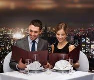 Uśmiechnięta para z menu przy restauracją Fotografia Stock