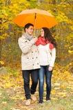 Uśmiechnięta para z parasolem w jesień parku Fotografia Royalty Free